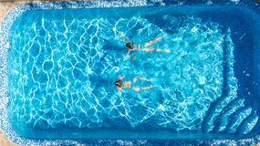 Active girls in swimming pool water aerial drone view from above, children swim, kids have fun on tropical family vacation. Holiday resort concept royalty free stock photo