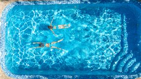 Active girls in swimming pool water aerial drone view from above, children swim, kids have fun on tropical family vacation. Holiday resort concept stock photography