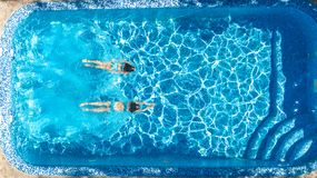 Active girls in swimming pool water aerial drone view from above, children swim, kids have fun on tropical family vacation. Holiday resort concept stock photo