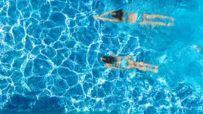 Active girls in swimming pool water aerial drone view from above, children swim, kids have fun on tropical family vacation. Holiday resort concept stock photos