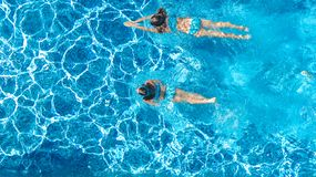 Active girls in swimming pool water aerial drone view from above, children swim, kids have fun on tropical family vacation. Holiday resort concept stock images