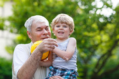 Active grandfather playing with little grandson ball Stock Image