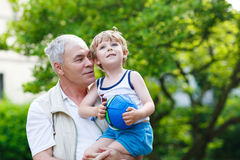 Active grandfather playing with little grandson ball Royalty Free Stock Image