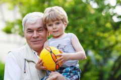 Active grandfather playing with little grandson ball Royalty Free Stock Images