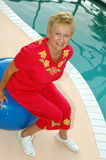 Active Grandma. A senior woman sits on an exercise ball by the pool royalty free stock photography