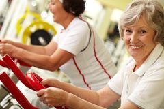 Active grandmas. Portrait of two good-looking senior women training on exercise machines Royalty Free Stock Photography