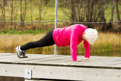 Active grandmum doing push-ups on fresh air. Stock Photo