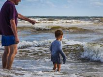 Active Grandpa and Grandson enthusiastic playing in sea waves. Inquisitive kid in wet clothes learn from Grandpa about sea waves. North-Sea, storm, morning royalty free stock photos