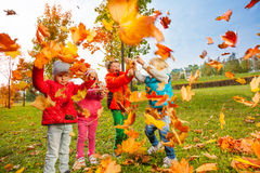 Active group of children play with flying leaves stock photos
