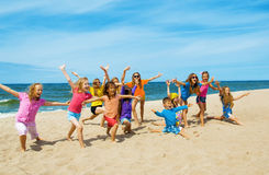 Active happy children on the beach. Active sporty children doing exercise on the beach stock photos