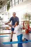 Active happy elderly couple exercising in gym. Cheerful senior women performing yoga exercise at fitness studio. People, sport, leisure, positive emotions royalty free stock image