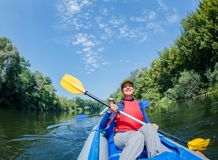 Summer vacation - Happy girl with her mother kayaking on river. Stock Photo