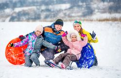 Happy family portrait outdoors at winter time. Active happy family smiling and laughing while playing outdoors during winter holidays. Winter fun outdoors with royalty free stock photo