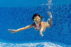 Active happy girl swims underwater in pool Stock Images
