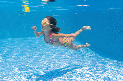 Active happy girl swims underwater in pool Royalty Free Stock Image
