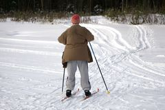 Active happy healthy grandpa , skiing in the snowy forest on a Sunny winter day stock images