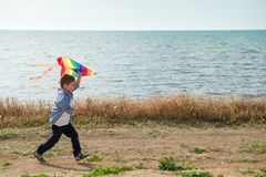 Active happy kid running with colourful kite in his hands along sea shore in spring. Active happy kid running with colourful kite in his hands along sea shore Royalty Free Stock Photo