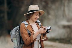 Active healthy Caucasian woman taking pictures with an vintage film camera on a forest rocks. Active healthy Caucasian woman with a backpack taking pictures with stock photos