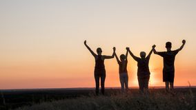 Active healthy family, grandmother with daughter and grandchildren meet the dawn, raise their arms above stock photos