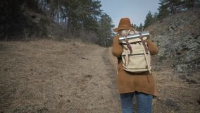 Active healthy hipster teen hiking in forest. Young girl traveler walks through the forest. A hat and a traveler`s. Backpack are put on. 120 FPS slow motion stock footage