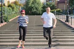 Active healthy lifestyle of mature couple. Middle-aged man and woman running upstairs stock image