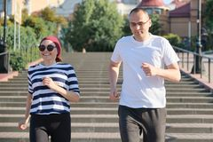 Active healthy lifestyle of mature couple. Middle-aged man and woman running upstairs stock photography