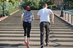 Active healthy lifestyle of mature couple. Middle-aged man and woman running upstairs, view from the back stock images