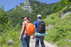 Active and healthy lifestyle on summer vacation and weekend tour. Group of tourists hitching a ride. Travel adventure and hiking a Royalty Free Stock Photo