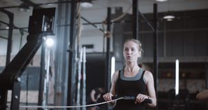 Active and healthy lifestyle, young beautiful happy blonde woman working out on rowing machine in gym slow motion. Motivation for success and staying fit stock footage
