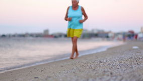 Active healthy senior woman walking on beach