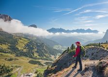Active hiker hiking, enjoying the view, looking at Dolomites mountains landscape royalty free stock images