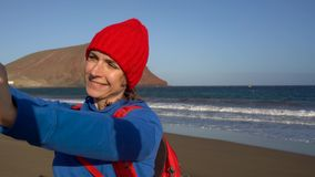 Active hiker woman walks on the beach and makes self photo on her smartphone. Caucasian young woman with backpack on stock footage