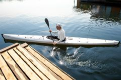 Man paddling a white kayak. Active hobby concept. New white canoe with paddle man departing from the pier stock image