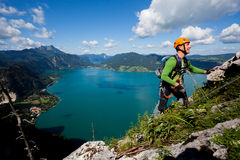 Active holiday. Young man climbing high above alpine lake Royalty Free Stock Photos