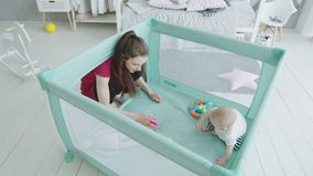 Baby girl playing with beloved mother in playpen stock video footage