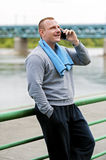 Active jogger talking by cell phone. Royalty Free Stock Photos