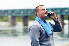 Active jogger talking by cell phone. Royalty Free Stock Photography