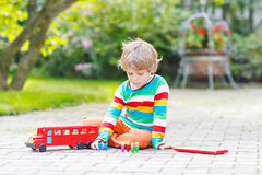 Active kid boy playing with red school bus and Royalty Free Stock Photo