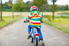 Active kid boy in safety helmet and colorful clothes on bike. On summer day. Active leisure for children outdoors Royalty Free Stock Images