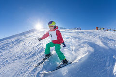 Active kid boy skiing in mountains at sunny day. Active kid boy with safety helmet, goggles and poles skiing in mountains at sunny day Stock Photos