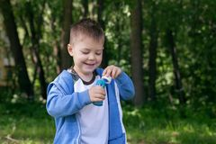 Active kid playing in the garden on a sunny summer day, Out doors activities for children. 4 years Little boy with soap bubbles in summer green trees park, funny royalty free stock images