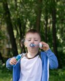 Active kid playing in the garden on a sunny summer day, Out doors activities for children. 4 years Little boy with soap bubbles in summer green trees park, funny royalty free stock photography