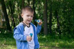 Active kid playing in the garden on a sunny summer day, Out doors activities for children. 4 years Little boy with soap bubbles in summer green trees park, funny stock photo