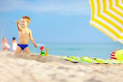 Active kid playing in sand on the beach. Active kid playing in sand on the colorful beach Stock Photo