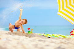 Active kid playing in sand on the beach Stock Photos
