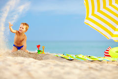 Active kid playing in sand on the beach Royalty Free Stock Photo