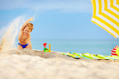 Active kid playing in sand on the beach Royalty Free Stock Photos