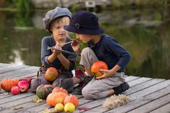 Active kids paint small Halloween pumpkins Royalty Free Stock Image