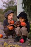 Active kids sitting with Halloween pumpkins Royalty Free Stock Images