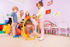Active kindergarten class kids crawl though hoops Stock Photo